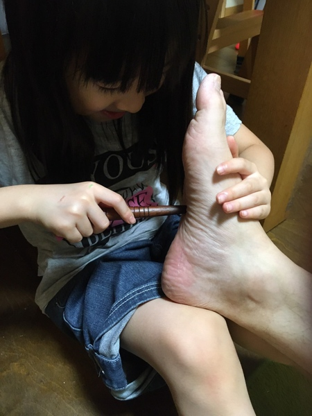 足を揉む娘